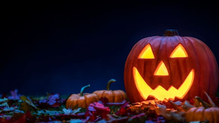 A smiling Jack O' Lantern sitting in the grass with small pumpkins and fallen leaves at night.
