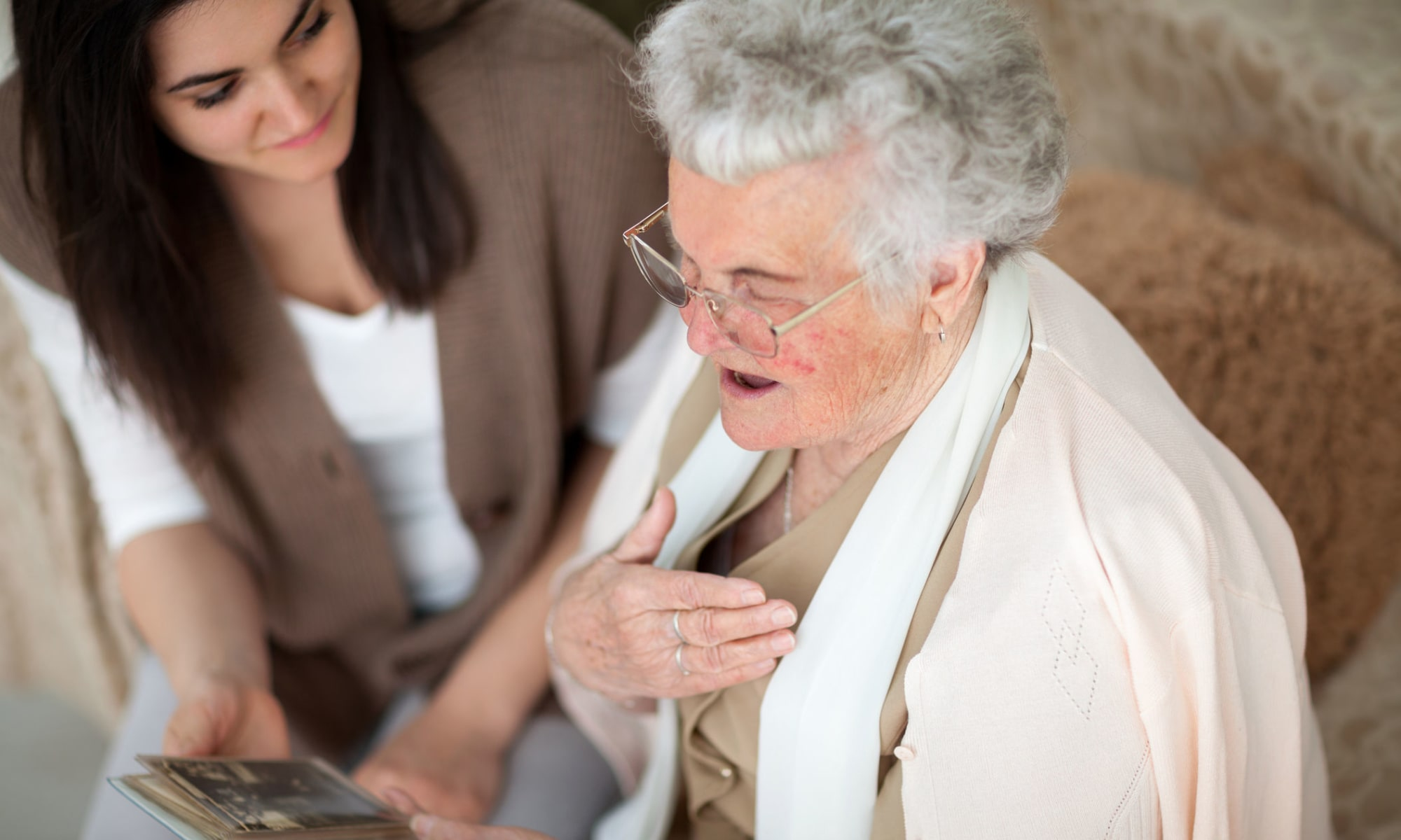 Caregiver and resident look at pictures together at Broadwell Senior Living in Kearney, Nebraska