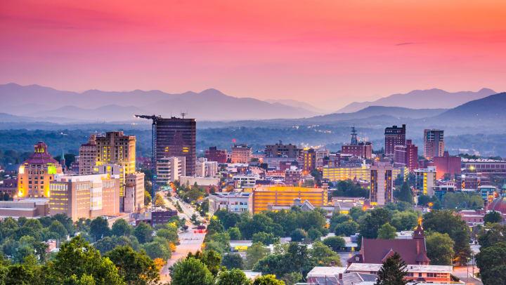 Asheville, North Carolina, skyline set against a mountainous backdrop at sunset.