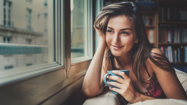Woman drinking coffee at home looking out the window