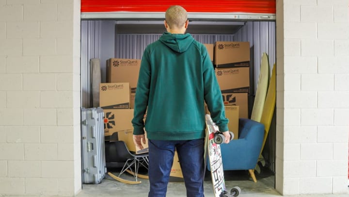 College student holding skateboard looking at storage unit