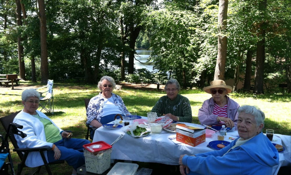 A group of residents eating outside at Keystone Commons in Ludlow, Massachusetts