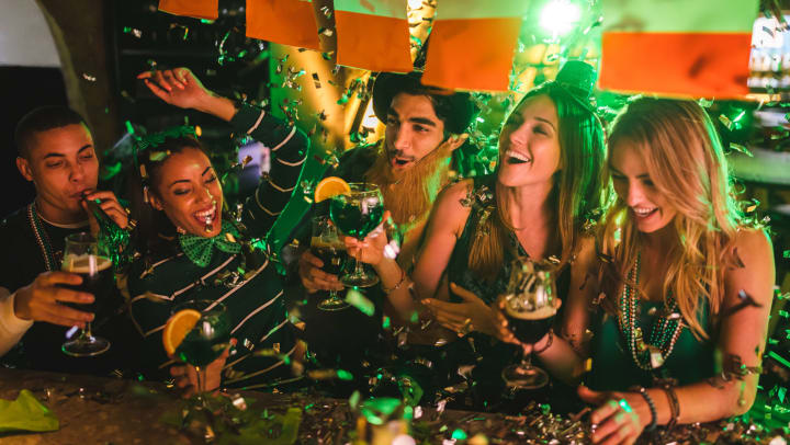 Friends partying with drinks and confetti on St. Patrick's Day