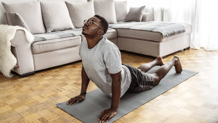 A man stretching on a yoga mat on the floor of an apartment with a sectional couch in the background