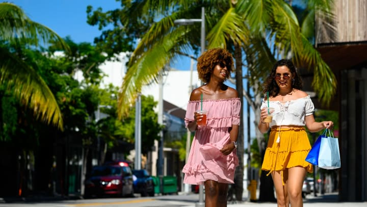 Two women walk down the street, both with drinks in their hands and the one on the right carrying shopping bags