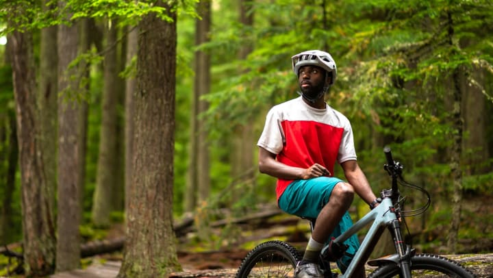 A man on a mountain bike in the middle of a forest.