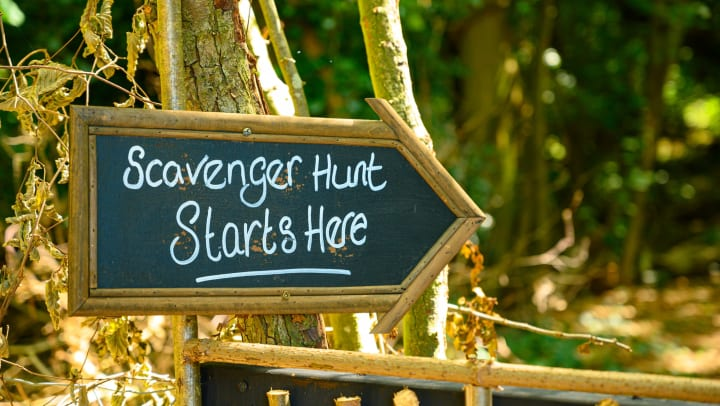 """Chalkboard sign that reads """"Scavenger Hunt Starts Here"""" nailed to a tree."""