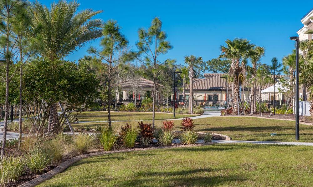 Courtyard with greenery and walking paths at Inspired Living at Lakewood Ranch in Bradenton, Florida
