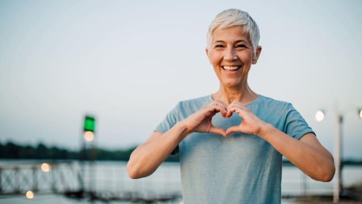 Senior woman holding hands in heart shape