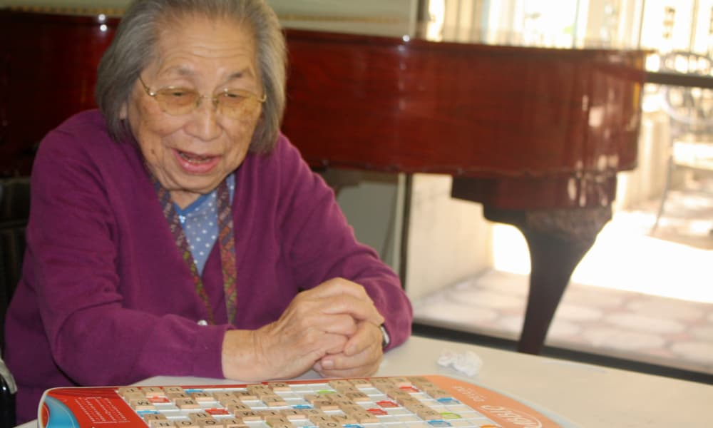 Resident playing Scrabble at Regency Park Astoria in Pasadena, CA