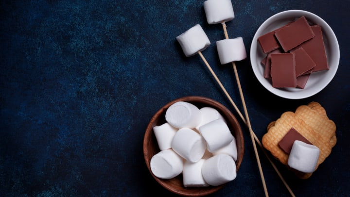 Marshmallows on sticks, chocolate pieces and marshmallows in bowls, and a stack of graham crackers, all on a dark background.