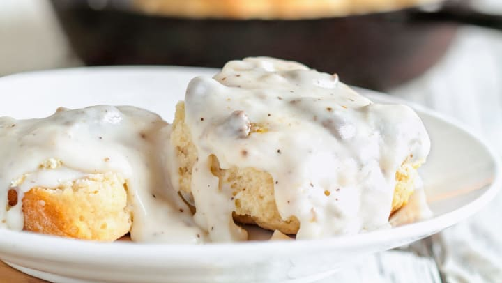 Gooey biscuits and gravy on a white plate.