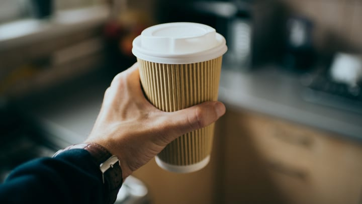 A man holding a cup of coffee to go.