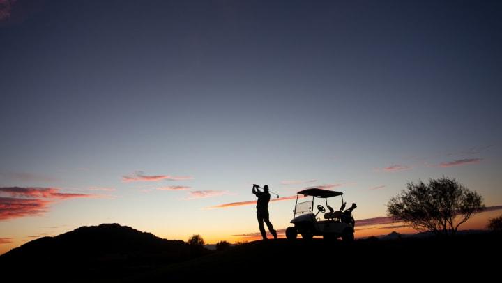 Golfer teeing off at sunrise near Vistara at SanTan Village in Gilbert, Arizona