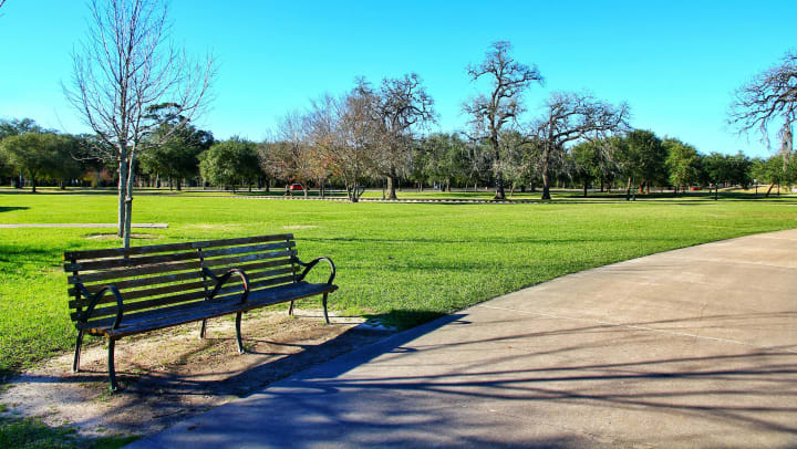Bench near a well manicured lawn and walking path at a park near Olympus Waterford in Keller, Texas