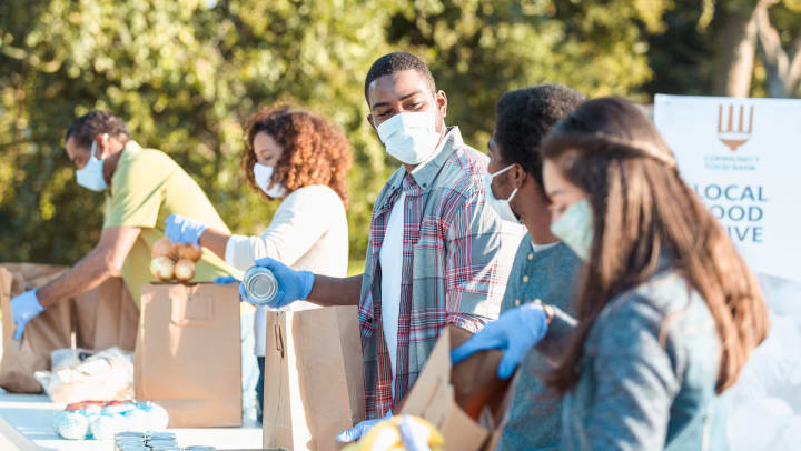 Group of volunteers packing donations items into boxes and bags, wearing gloves and masks