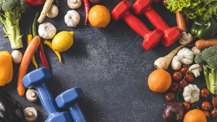 A colorful assortment of fruits and vegetables on a slate background with red and blue dumbbells