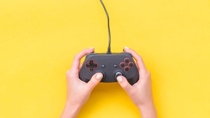 Hands holding generic gamepad. Yellow background.