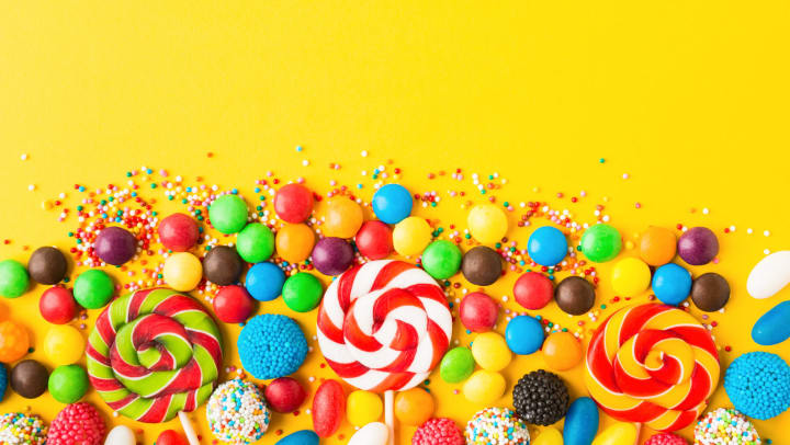 Colorful candies over yellow background. Top view. Flat lay.