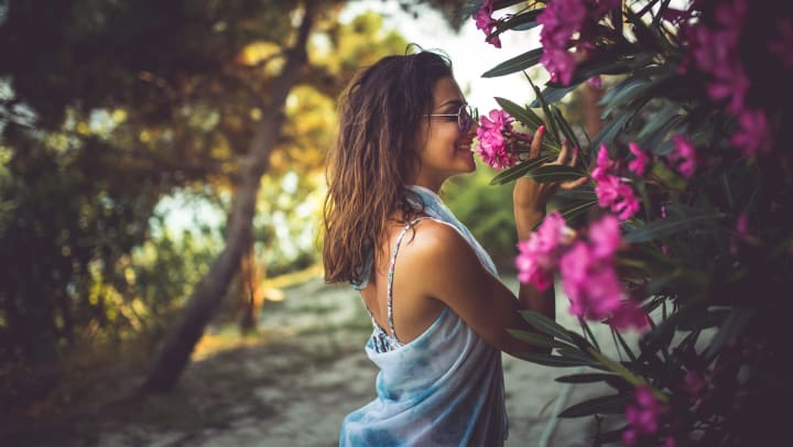 Woman with sunglasses stopped to smell pink flowers on a trail.