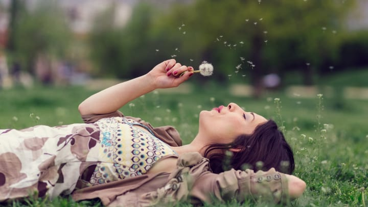 Woman lying in the grass blowing on a dandelion.