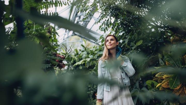 Woman walks through a garden setting