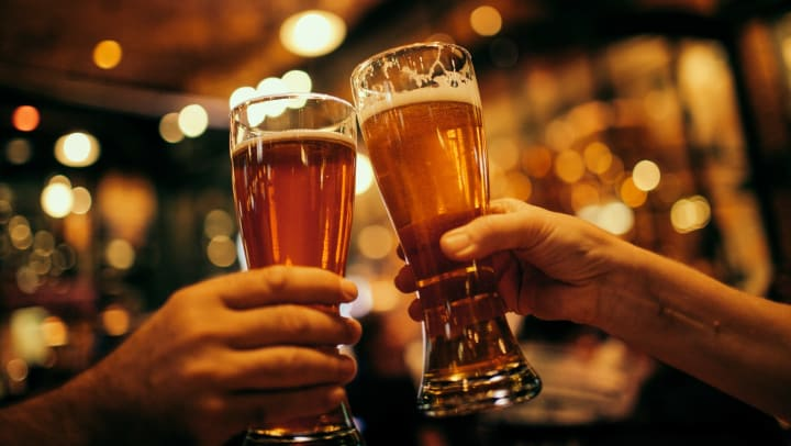 View inside a bar with two hands holding beer mugs and touching the mugs together
