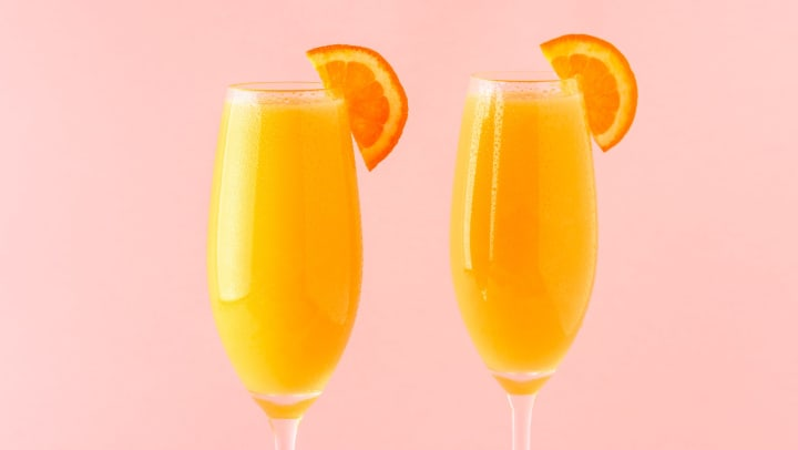 Two glasses filled with orange liquid and an orange slice on the rim in front of a pale pink background.