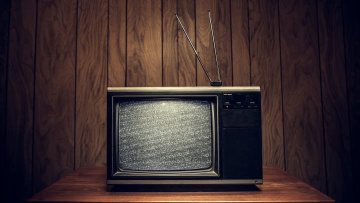 Vintage TV with static on the screen, wood paneling in the background.