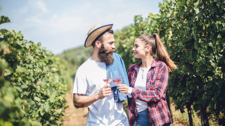 A man and woman couple drinking wine while walking between rows of grape vines.