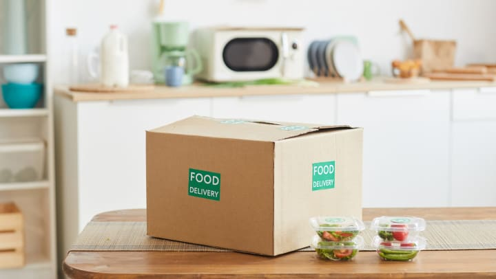 """A large cardboard box that reads, """"Food Delivery"""" sitting on a kitchen counter."""