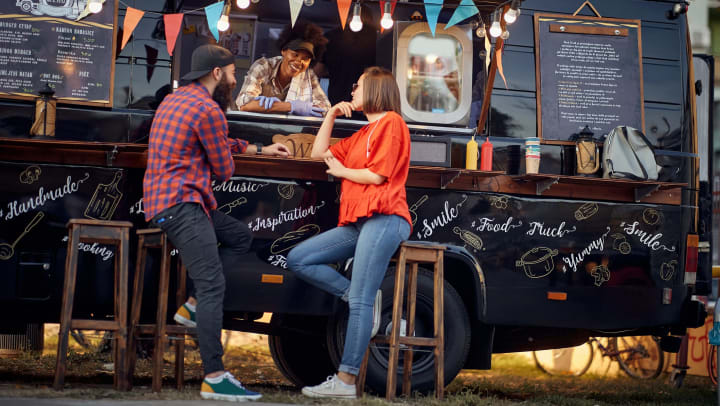 Two people seated in front of a food truck talking to the server inside.