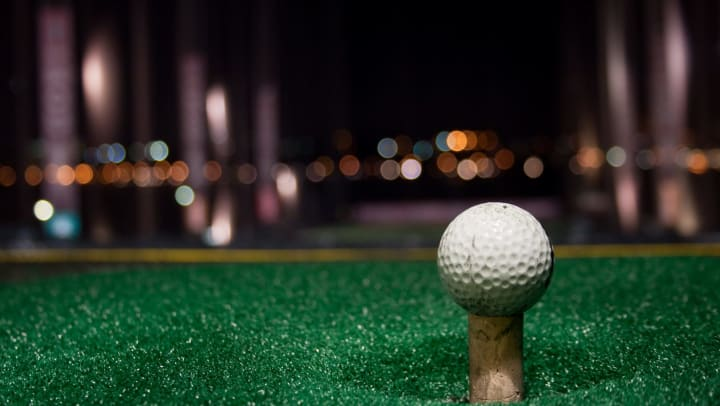 A golf ball on a tee at a driving range at night