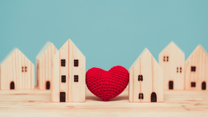 Knitted heart between wooden model homes, blue background.