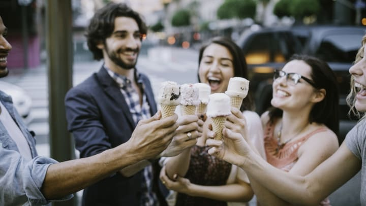 Group of men and women toasting their ice cream cones and smiling on the sidewalk.