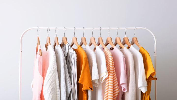 Fashion clothes on a rack in a light background indoors.