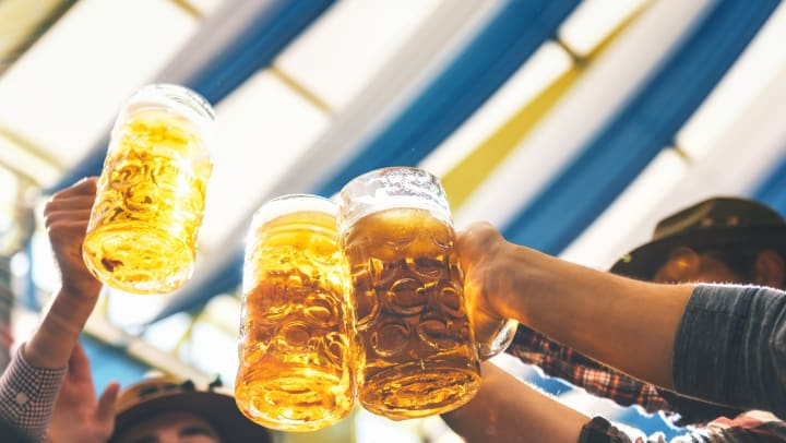 Several hands raise a toast with large, glass beer steins at Oktoberfest.