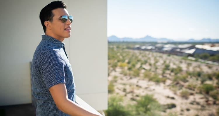 Resident admiring the view from his private balcony at San Hacienda in Chandler, Arizona
