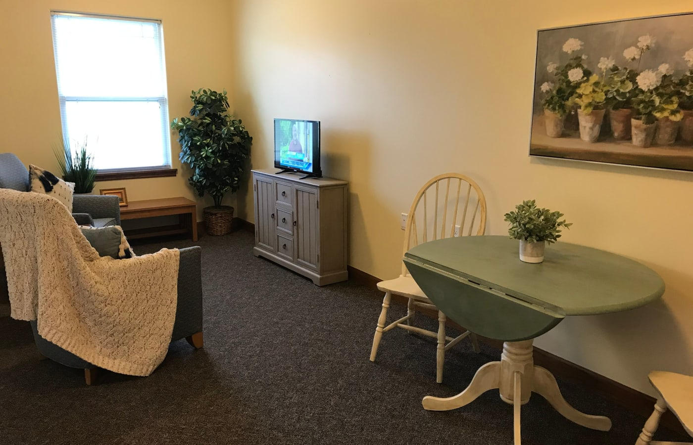 A dining area and living room in an apartment at Prairie Hills Senior Living in Des Moines, Iowa