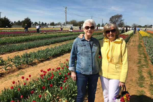 Two residents from Liberty Heights Gracious Retirement Living in Rockwall, Texas in a flower field
