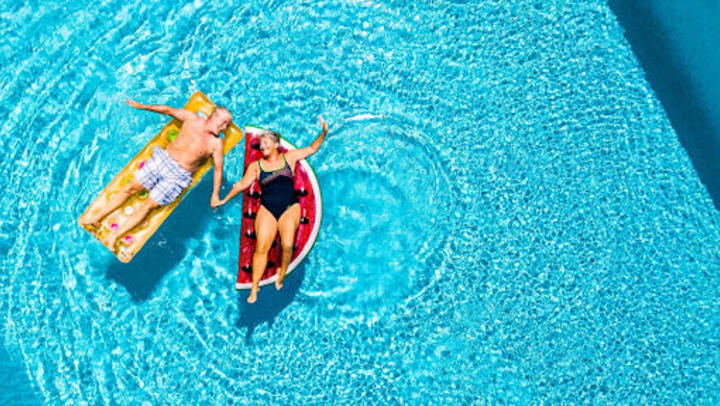 An aerial view of a smiling couple enjoying the summer on pool floats in the water.