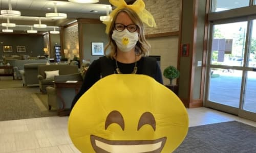A staff member dressed up as a smiley face at Merrill Gardens.
