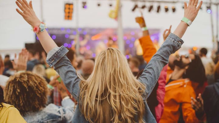 Woman with outstretched arms dancing at a festival near {{location_name}} in {{location_city}}, {{location_state_name}}.