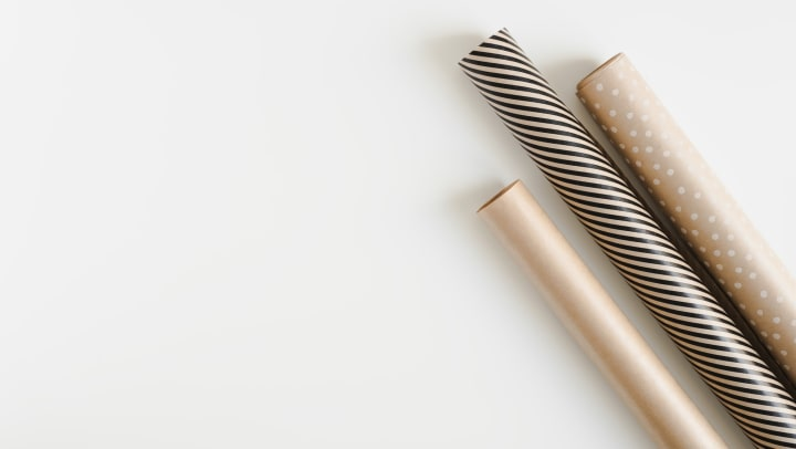 Classy gold white and black wrapping paper rolls on a white background