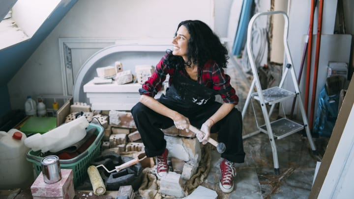 Smiling woman with mallet in hand surrounded by painting supplies and loose bricks.