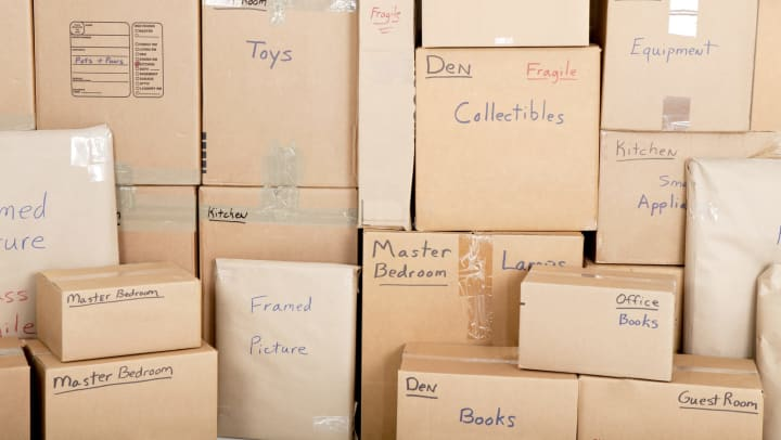 A wall of stacked boxes all labeled with different rooms of a house and types of items.