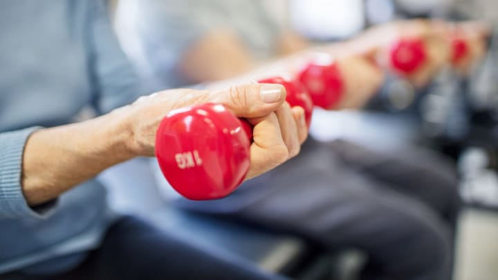 Close up of two women seated lifting up a pair of red dumbbell weights