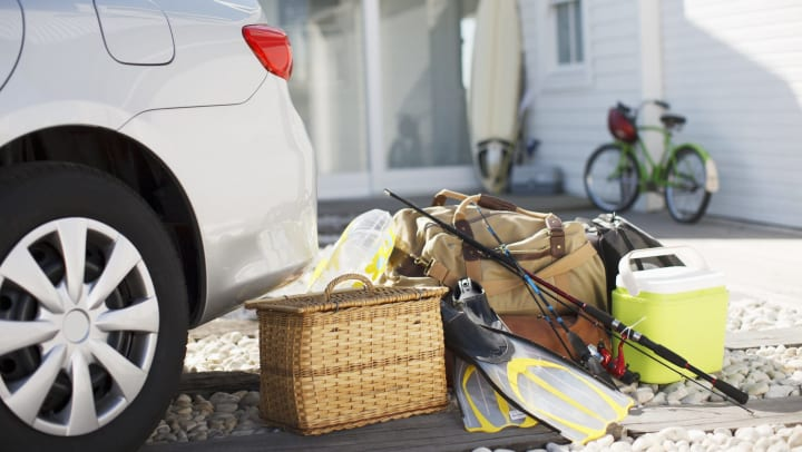 A picnic basket, fishing rod, flippers, and bags sit behind a car in a driveway, with a bicycle and paddleboard in the background.