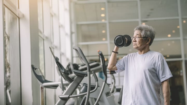 Senior man working out with dumbbell in a contemporary gym