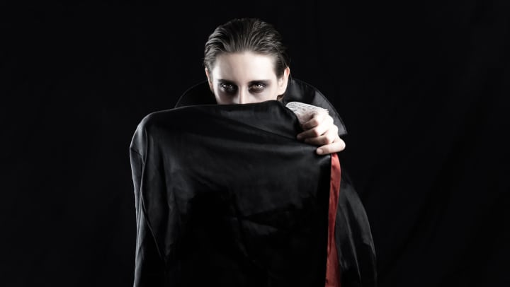 Dracula, holding his cape over his face